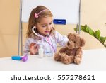 little girl treats a bear ... | Shutterstock . vector #557278621