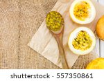 Small photo of Passion fruits and slice with wooden spoon on wooden background.