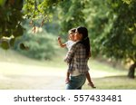 mother holding her daughter and ... | Shutterstock . vector #557433481
