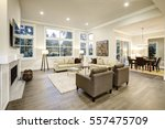 Small photo of Chic light living room design with dark floors. Furnished with glass top accent tables and beige sofas topped with brown pillows . Northwest, USA