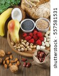 Small photo of Foods rich in fiber as rye bread, wheat bran, white beans, red beans, spinach, almonds, poppy seed, pears, bananas, coconut, raspberries, pistachios, walnuts. Wooden table as background