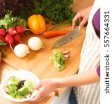 young woman cutting vegetables...   Shutterstock . vector #557664331