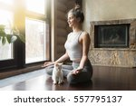 Stock photo young attractive smiling woman practicing yoga sitting in half lotus exercise ardha padmasana 557795137