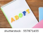Small photo of Word ADOPT and notepads on wooden background