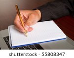A man writing in a notebook - stock photo