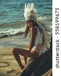 Small photo of Fashion portrait of beautiful girl in costume of American Indian