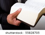 A man holding a large book, like the holy bible - stock photo