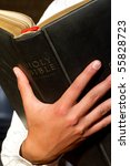 A close up of a man holding the holy bible - stock photo