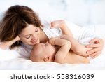 mother and child on a white bed.... | Shutterstock . vector #558316039