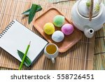 Small photo of Mo chi dessert,stuffed eggs on bamboo with tea set and blank copy space notebook