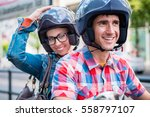 Small photo of Smiling girl with glasses sitting on pillion seat of scooter