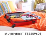 open suitcase with clothes and... | Shutterstock . vector #558809605