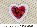 Small photo of Elixir of love, Red philter in heart bowl on bamboo mat.