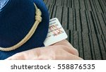 Small photo of At the airport before the flight. Boarding card and a blue summer hat.