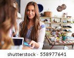 teenage young woman paying with ... | Shutterstock . vector #558977641