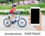 Small photo of woman use mobile phone and blurred image of a boy ride the bicycle in the park