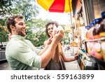 Couple Buying A Hot Dog In A...