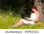 The beautiful young woman sits on a grass in a park with the laptop. - stock photo