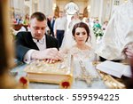 Small photo of Wedding couple at church swear allegiance each other holding hands on Gospel.
