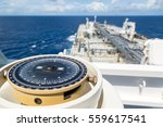 Small photo of Compass aboard a ship on a blue summer sea.
