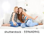 Two Cute Girls Sitting On Sofa