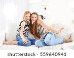 Two Cute Girls Sitting On Sofa