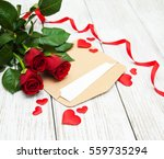 Stock photo red roses and greeting card on a wooden table 559735294