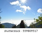 Stock photo a back view of long hair and tall woman standing at the peak of the mountain and the blue sky with 559809517