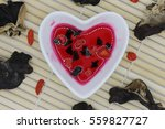 Small photo of Elixir of love, Red philter in heart bowl and ingredient on bamboo mat.
