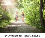 two girls riding bikes on a... | Shutterstock . vector #559855651