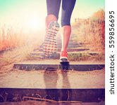 Small photo of woman with athletic pair of legs going for a jog or run during sunrise or sunset up stairs in the mountains, healthy lifestyle concept toned with a retro vintage instagram filter app or action effect