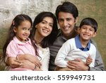 family of four smile at camera | Shutterstock . vector #559949731