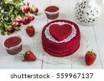 """Red cake without cream """"red velvet"""" on a white wooden table, decorated with strawberries, roses and white openwork vase with a heart of cakes and muffins. Cake on a holiday Valentine"""