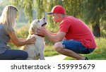 Small photo of Young couple spend time outdoors with their pet dog. Man and woman affectionately stroking labrador or golden retriever at nature. Guy and girl petting their domestic animal. Relax together at summer