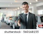 confident car dealer giving a... | Shutterstock . vector #560168155