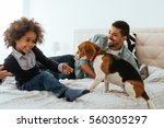 Stock photo african american father and daughter spending time together with a dog on a bed 560305297