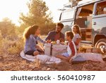 family having a picnic beside... | Shutterstock . vector #560410987