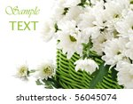 Green wicker basket filled with fresh cut flowers on white background with copy space. - stock photo