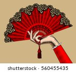 female hand with red open fan.... | Shutterstock . vector #560455435