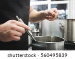 pouring spices to the soup | Shutterstock . vector #560495839