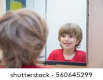 young boy looking at himself in ... | Shutterstock . vector #560645299