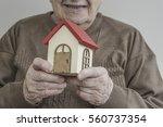 a senior woman holding small... | Shutterstock . vector #560737354