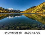A large, clear mountain lake leads to a golden aspen colored mountain, snow capped peaks and a big beautiful blue sky. - stock photo