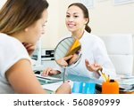 Small photo of Young cheerful woman looking at mirror during consultation with beautician in aesthetic medicine center