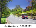 Golf Estate with forest and course with Buggy in the foreground - stock photo
