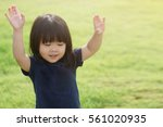 little girl praying and raise... | Shutterstock . vector #561020935