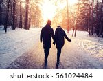 couple holding hands walking... | Shutterstock . vector #561024484