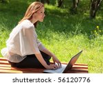 Pretty young woman with a laptop at park - stock photo