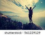cheering young woman backpacker ... | Shutterstock . vector #561229129