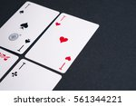 Small photo of High Angle View of Four Playing Cards Spread Out on Dark Background Showing Aces from Each Suit - Hearts, Clubs, Spades and Diamonds
